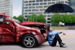 Man with damaged car sits under umbrella Royalty Free Stock Image
