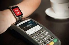Man danandebetalning till och med smartwatch via NFC-teknologi Arkivbild