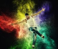 Man dancer showing break-dancing moves. Against colourful powder explosion Stock Photo