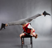 Man dancing on chair. Young man upside down on chair improvisational dancing, studio background stock photo