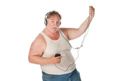 Man dancing to music on handheld audio device. Fat man with mp3 player dancing to music Royalty Free Stock Images