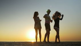 Man dancing with two women on a beach at sunset. Man dancing with two women on the beach at sunset stock video