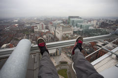 Man dangling feet over city view. Man dangling his feet off the side of a building with a city view stock image