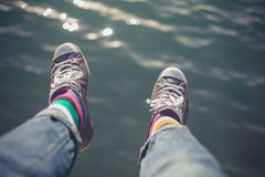 Man dangling feet over water. The feet of a young man dangling over water stock photo