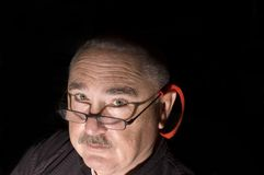 Man in the dark. Mustached Man wearing glasses in the dark with direct light looking up Stock Photography