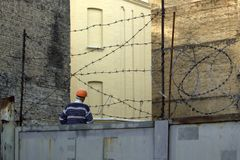 Man in orange helmet in construction site behind barbed wire royalty free stock photo