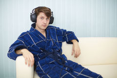 Man in dark blue dressing gown listens to music Stock Photos
