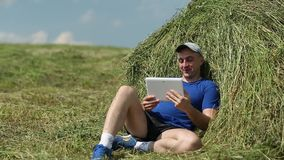 Man in dark blue t-shirt sits near haystack and communicates via tablet computer stock footage