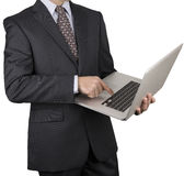 Man in a dark business suit pointing at a laptop Royalty Free Stock Photography