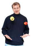 Man in dark cloth juggle apple. On white background Stock Photography