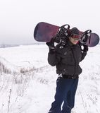 Man in dark clothes with a snowboard ski Stock Image