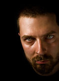 Man in the dark with evil eyes. Low-key portrait of sinister man with scary eyes Stock Photography