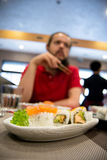 Man with dark hair and long beard in front of a plate with tasty sushi in a restaurant Royalty Free Stock Images