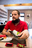 Man with dark hair and long beard holding a plate with tasty sushi in a restaurant Royalty Free Stock Photography