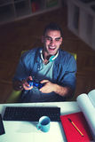 Man in the dark office playing video games Stock Photos