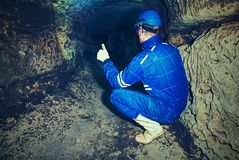 Man in dark old tunnel. Bastion passage under city  Stairs to the tunnel. With walls made of orange sand stone. Staff in blue overall and safety helmet Royalty Free Stock Images