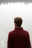 Man in dark red blouse looking at lake / Thinking men in red pullover standing with back and looking at water / Young man meditat stock photo