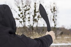 Man in a dark robe raised his hand with a big black knife up Royalty Free Stock Images