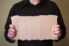 A man in a dark shirt holding a piece of cardboard. Prepared for your text stock photography