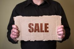 A man in a dark shirt holding a piece of cardboard with text Sale royalty free stock image