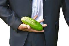 Man in dark suit with cucumber. Man in dark suit shows big fresh cucumber in his hand Stock Photos