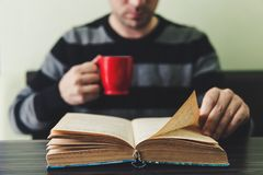 Man in dark sweater sitting by wooden table and reading book. Man in dark striped sweater sitting by wooden table and reading book while holding mug. Evening Stock Photography