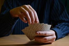 Man in darkness holding a set of playing cards and chooses one of them, business strategic competition concept stock image