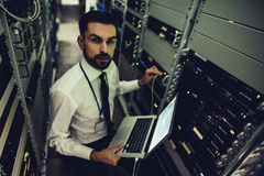 Man in data centre. Handsome man is working in data centre with laptop.IT engineer specialist in network server room.Running diagnostics and maintenance royalty free stock photography