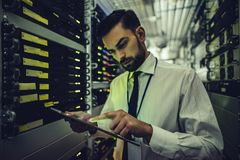 Man in data centre. Handsome man is working in data centre with tablet.IT engineer specialist in network server room.Running diagnostics and maintenance royalty free stock photography