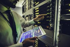 Man in data centre. Handsome man is working in data centre with tablet.IT engineer specialist in network server room.Running diagnostics and maintenance royalty free stock images