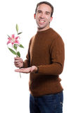 Man On A Date. A young man offering a lily to someone unseen, isolated against a white background Royalty Free Stock Images