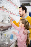 Man and daughter deciding on best bird to keep. Positive men and daughter deciding on best bird to keep in pet store Stock Image