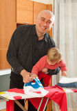 Man and  daughter ironing Stock Photography