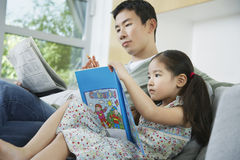 Man And Daughter With Picture Book And Newspaper Royalty Free Stock Image