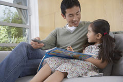 Man And Daughter With Picture Book On Sofa Stock Photography