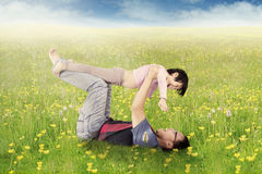 Man and daughter playing on blossom meadow Royalty Free Stock Photography