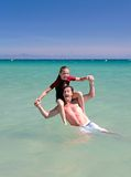 Man and daughter playing in the sea on vacation Stock Image