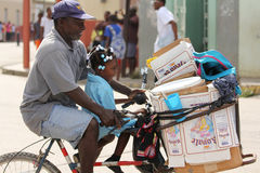 Man with daughter riding bicycle. FALMOUTH, JAMAICA, MAY 11: An unidentified man with daughter riding bicycle outside the port of Falmouth on MAY 11, 2011 in Stock Photos