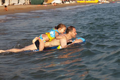 Man with daughter riding on an inflatable raft Royalty Free Stock Photo