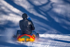 Man with daughter sledding down a snowy hill Royalty Free Stock Photo