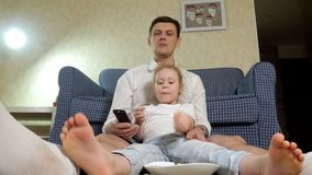 Man and daughter watching television, sitting on the floor eating snacks. 4k stock video footage