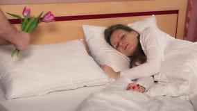 Man de echtgenoothand zette tulpenbloemen op hoofdkussen dichtbij slaap vrouwelijke vrouw op bed stock videobeelden