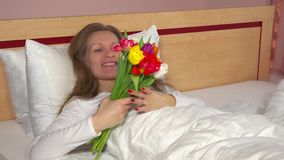 Man de hand geeft zijn vrouwenboeket van tulpenbloemen Gelukkige vrouw in bed stock footage