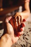 Man de hand van de holdingsvrouw ` s met trouwring op de vinger Stock Fotografie