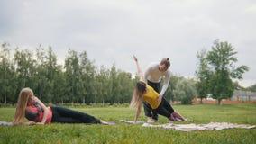 Man de instructeur leidt jonge vrouwen voor flexibiliteit op - yogapraktijk in ochtendpark stock video