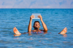 Man At The Dead Sea, Israel. Man floating with the tablet in the waters of the Dead Sea, Israel Royalty Free Stock Photo