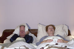 Man Dealing with Snoring Wife. Mature couple in bed with wife snoring and husband covering ears Stock Photos