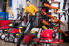 Man deciding on best lawnmower in garden equipment shop Royalty Free Stock Photography