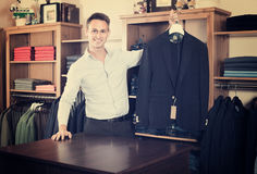 Man is deciding on for new dark blue suit. In male clothes store Stock Image
