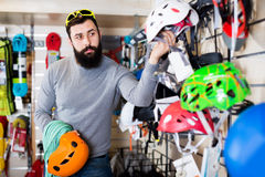 Man deciding on new helmet. Happy guy deciding on new helmet in sports equipment store Royalty Free Stock Photography